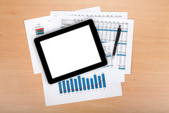 Tablet with blank screen over papers with numbers and charts Royalty Free Stock Image