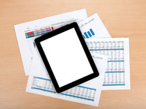 Tablet with blank screen over papers with numbers and charts Royalty Free Stock Photography