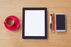 Tablet with blank screen, smart phone on wooden table. Office desk mock up. View from above Royalty Free Stock Images