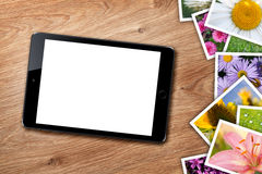 Tablet with blank screen and stack of printed pictures collage Stock Photography