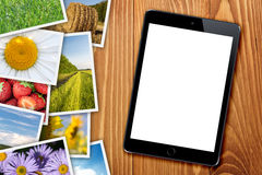 Tablet with blank screen and stack of printed pictures collage Royalty Free Stock Image
