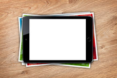 Tablet with blank screen and stack of printed pictures collage Royalty Free Stock Photos