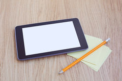 Tablet with blank screen on wooden table. Office desk mock up Stock Images