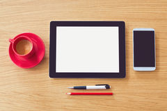 Tablet with blank screen on wooden table. Office desk mock up. View from above