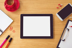 Tablet with blank white screen on wooden table. Office desk mock up. View from above. Tablet with blank white screen with pen and coffee on wooden table. Office