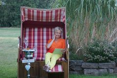 The attractive woman sits with the tablet in the roofed wicker beach chair and is happy about the birthday greetings. On a tablet, the blonde women in the roofed royalty free stock photos