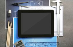 Tablet with blueprints and engineer equipment Stock Images