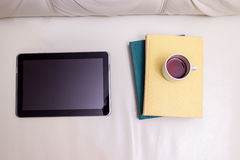 The tablet and books with a cup of black coffee on a light leather sofa. royalty free stock photo