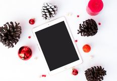 Tablet for branding in Christmas time. pines cones and christmas decorations in background/ stock images