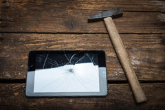 Tablet with broken glass. Hammer and tablet on the wooden table with broken glass Royalty Free Stock Photography