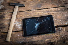 Tablet with broken glass. Hammer and tablet on the wooden table with broken glass Royalty Free Stock Photos