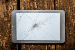 Tablet with broken glass. Tablet on the wooden table with broken glass Royalty Free Stock Image