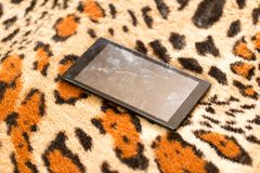 Tablet with a broken screen on the background of tiger skin.  royalty free stock photos