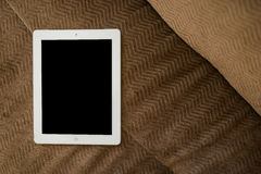 Tablet on brown sofa Stock Photography