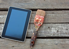 Tablet. And brush on wood background Royalty Free Stock Photo