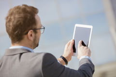 Tablet, business, businessman, man, computer, technology, person. Businessman using white digital tablet outdoors. Back viewpoint Stock Image
