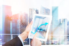 Tablet business graph. Businessperson using tablet with business chart on New York city background. 3D Rendering Stock Images