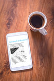 Tablet with business news. And black coffee on wooden table. Top view Royalty Free Stock Photography