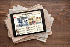 Tablet with business news website on stack of newspapers. All contents are made up. Business news concept stock images