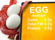 Tablet with Calories In egg  and measuring tape. On white background. nutrition facts Stock Image