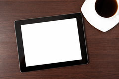 Tablet and a cap of caffe on the table Stock Image