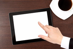 Tablet and a cap of caffe on the table and hand of a businessman Stock Photo
