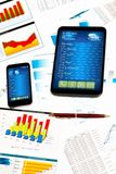 Tablet, cell phone and financial documents Stock Photos