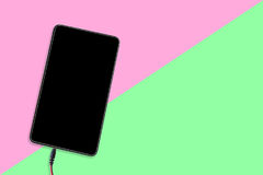 Tablet or cell phone on pink and green background Stock Photos