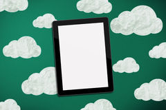 Tablet on chalk board with clouds Royalty Free Stock Photos