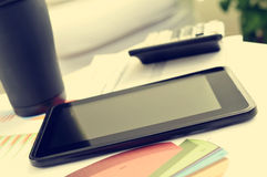 Tablet and charts at the office desk Royalty Free Stock Image