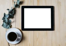 Tablet with a clean blank screen mockup monitor with a branch of eucalyptus and a cup of coffee on a wooden background. With natural wood planks top view royalty free stock images