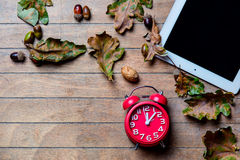 Tablet, clock and fallen leaves Stock Photo