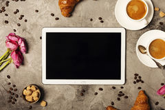 Tablet, coffee and croissants Royalty Free Stock Photos