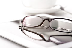 Tablet, coffee cup and glasses on a white table Stock Images