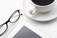Tablet, coffee cup and glasses on a white table Royalty Free Stock Photos