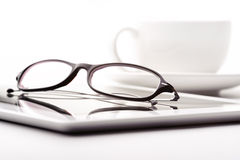 Tablet, coffee cup and glasses on a white table Stock Photo