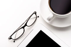 Tablet, coffee cup and glasses on a white table Stock Image