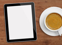 Tablet and coffee cup. On wood with blank screen Royalty Free Stock Photos