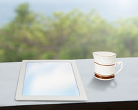 Tablet with coffee mug on window side table. Tablet with coffee mug on table with nature view outside Royalty Free Stock Images