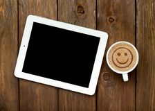 Tablet and coffee with smile sign. On wooden table Royalty Free Stock Photography