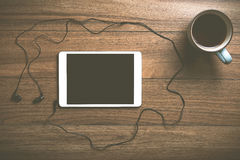 Tablet with coffee on wood with headphones Stock Photos