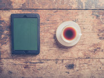 Tablet and coffee on wooden table Royalty Free Stock Images