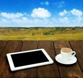 Tablet and coffee on a wooden table with natural background Stock Image