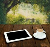 Tablet and coffee on a wooden table with natural background Stock Photo