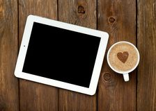 Tablet and coffee on a wooden table Royalty Free Stock Images