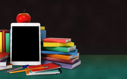 Tablet, colorful books, school supplies and apple on the table o Royalty Free Stock Photo