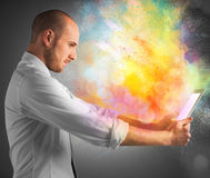 Tablet colour burst. Tablet with burst of bright colorful powders Stock Photo