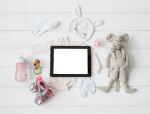 Tablet computer and baby`s items. On white Stock Images