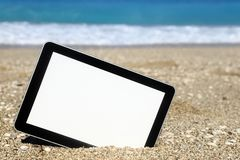 Tablet computer on the beach. In front of the sea Stock Photo