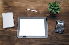 Tablet computer with blank screen. Business ideas concept. Mobile tablet computer with copy space, calculator and notepad with blank pages on wooden office desk Stock Images